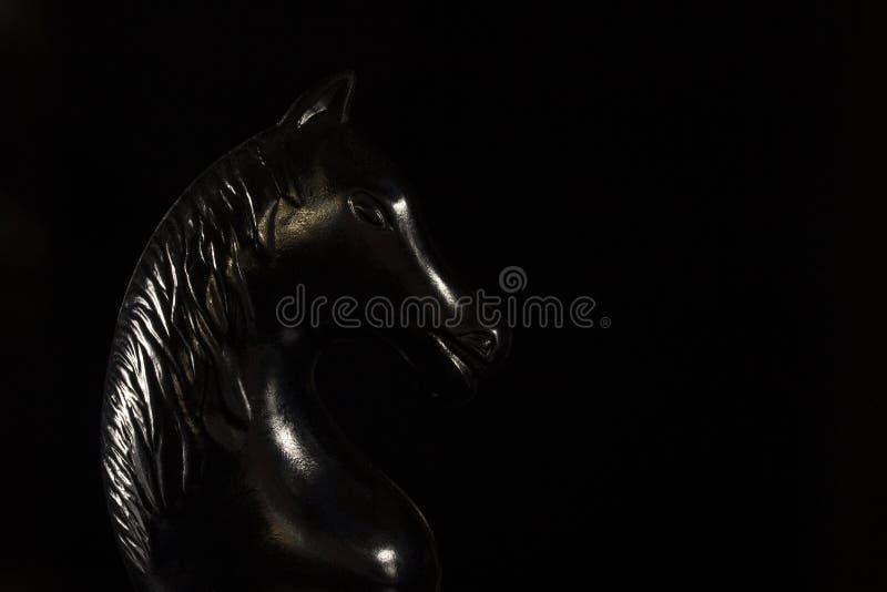 Cavaliere nero di scacchi su un fondo scuro fotografia stock