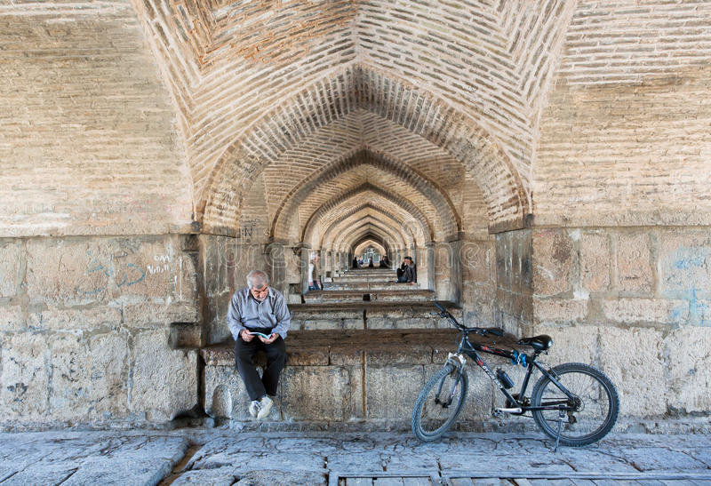 Cavaliere senior che legge un libro nella calma, sotto il ponte di pietra fotografia stock libera da diritti