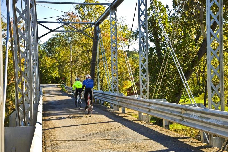 Cavalieri della bicicletta su un ponticello fotografie stock libere da diritti
