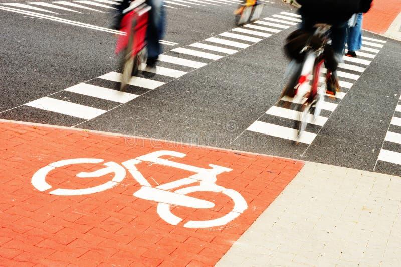 Cavaliers de panneau routier et de vélo de bicyclette photo stock