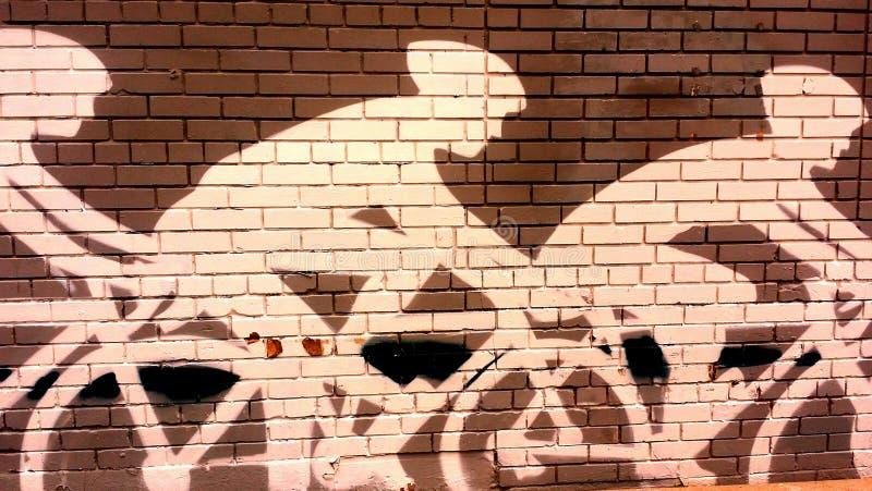 Cavaliers de vélo muraux sur le mur de briques photo stock