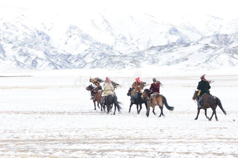 Cavaliers mongols de cheval dans les montagnes pendant le festival d'aigle d'or photographie stock libre de droits