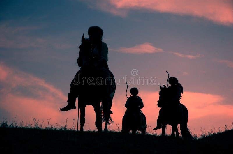 Cavaliers nomades de conduite sur le coucher du soleil photo libre de droits