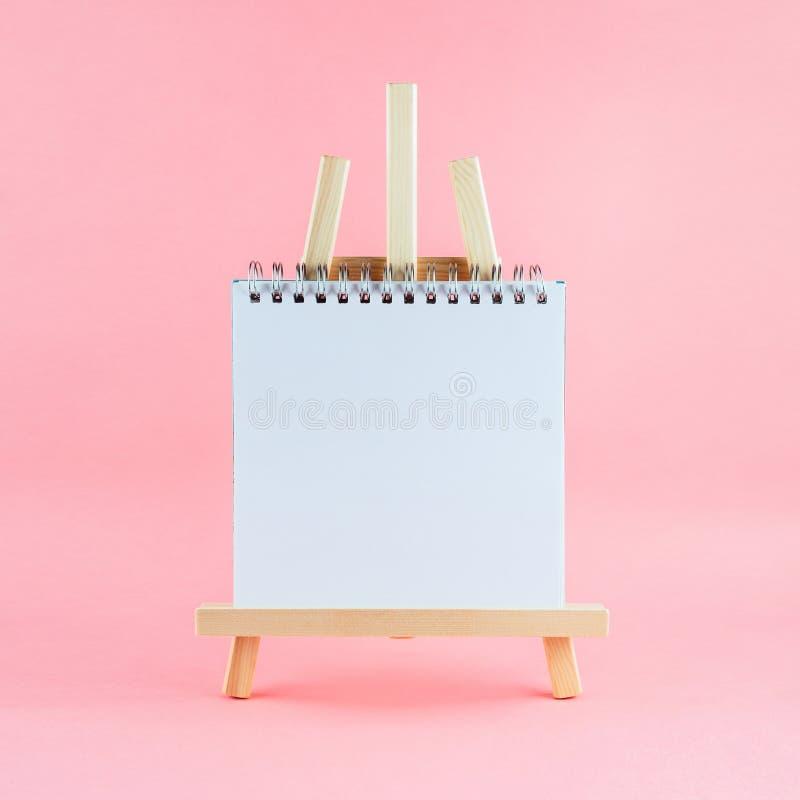 Cavalletto di legno di disegno con lo sketchbook della pagina in bianco su fondo rosa fotografia stock libera da diritti