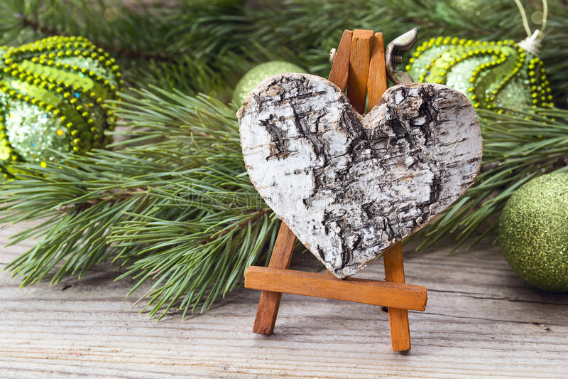 Cavalletto miniatura con il cuore della corteccia, i rami del pino ed il Natale dicembre immagine stock