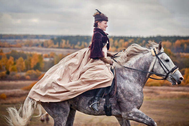 Cavallo-caccia con i cavalieri nell'abitudine di guida immagini stock libere da diritti
