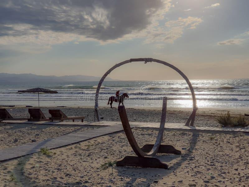Cavallo che passa sotto un arco di legno come galoppa lungo la spiaggia di Ayia Eirini immagini stock libere da diritti