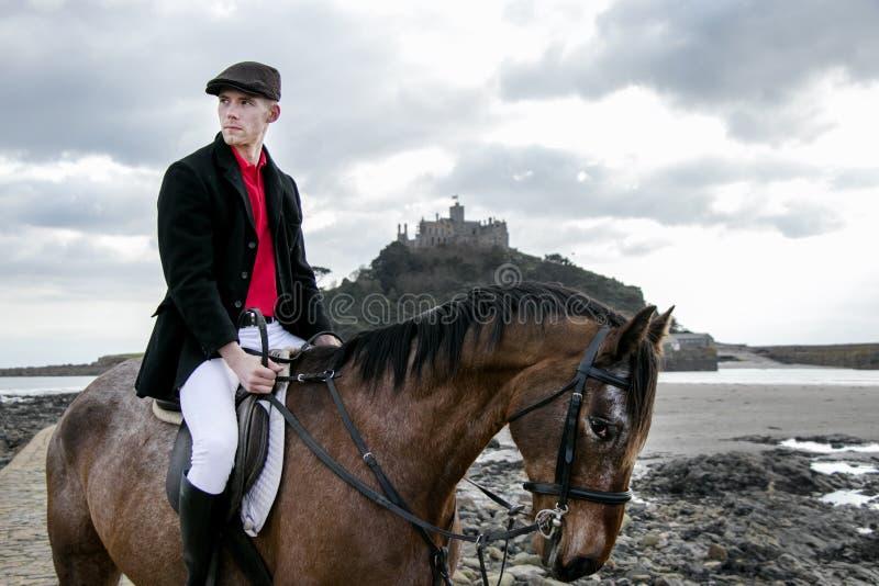 Cavallo da equitazione bello del cavaliere del cavallo maschio sulla spiaggia di modo tradizionale con il supporto del ` s di St  fotografia stock