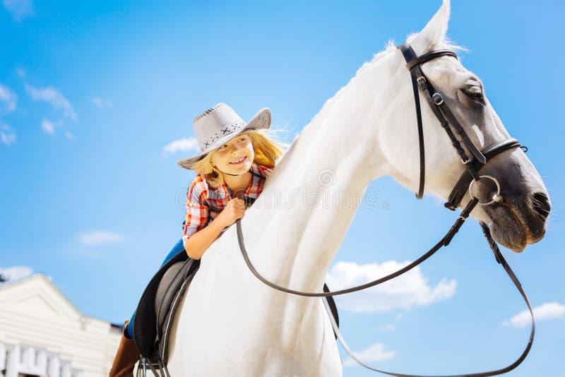 cavallo da equitazione bianco stupefacente ritenente della ragazza sveglia Bionda-dai capelli fotografie stock libere da diritti