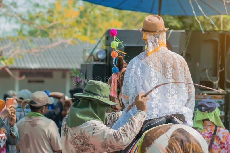 Cavallo da equitazione del giovane con la banda di musica nella cerimonia di classificazione nel rituale tailandese buddista del  fotografia stock libera da diritti