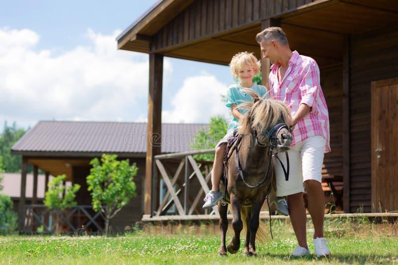 Cavallo da equitazione emozionante di sensibilità riccia bella del ragazzo vicino al padre immagini stock