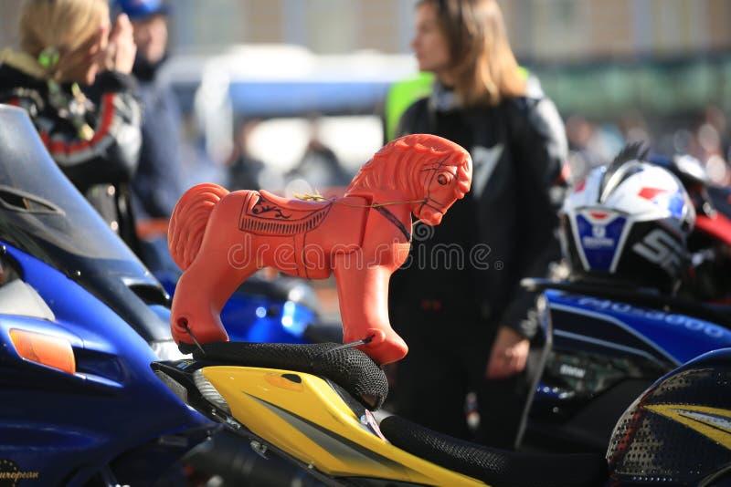 Cavallo di plastica rosso del giocattolo sulla sella del motociclo, fine su fotografia stock libera da diritti