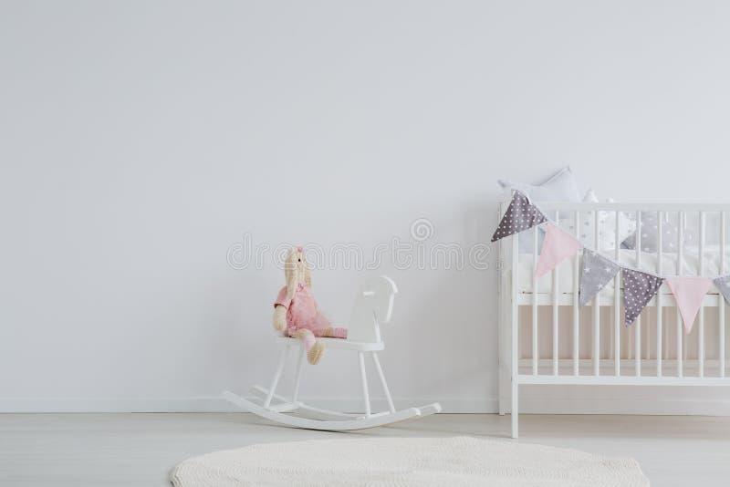 Cavallo a dondolo accanto al letto fotografia stock libera da diritti