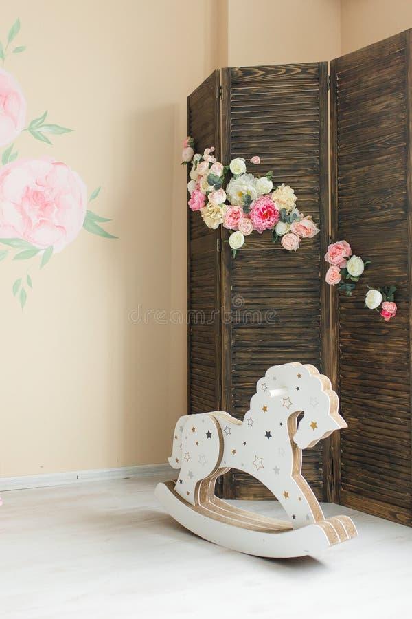 Cavallo a dondolo d'annata sul pavimento di legno nella stanza del bambino retro immagine filtrata fotografie stock