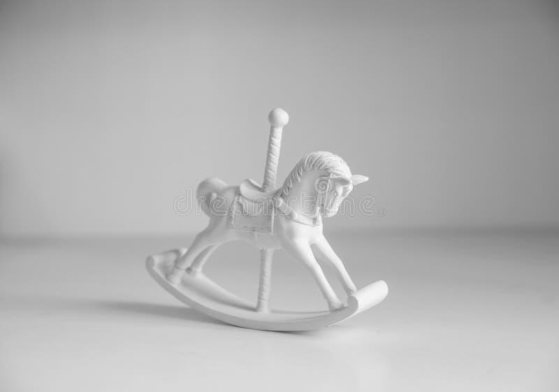 Cavallo a dondolo di legno sulla tavola bianca fotografia stock libera da diritti