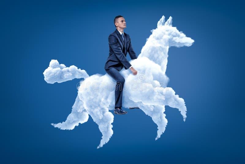 Cavalo branco da nuvem da equitação nova do homem de negócios no fundo azul imagens de stock