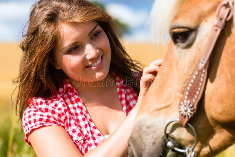 Cavalo das trocas de carícias da mulher - exploração agrícola do pônei imagens de stock