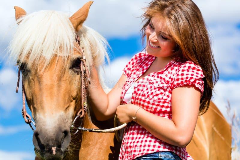 Cavalo das trocas de carícias da mulher na exploração agrícola foto de stock royalty free