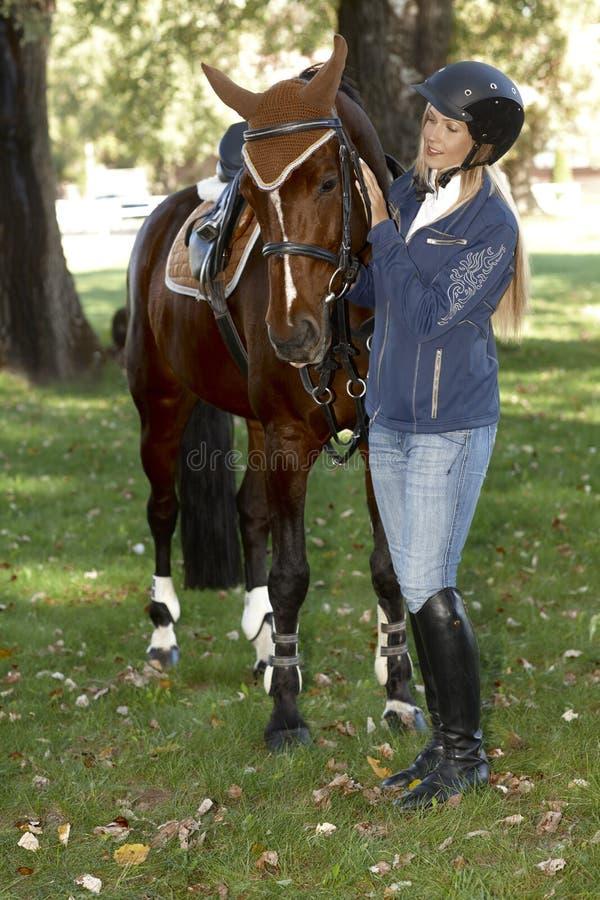 Cavalo de acariciamento do cavaleiro bonito foto de stock royalty free
