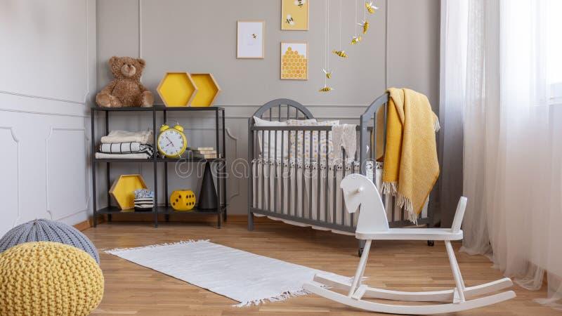 Cavalo de balanço branco na sala cinzenta e amarela elegante do bebê com prateleira industrial e o berço de madeira fotografia de stock royalty free