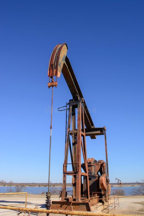 Cavalo de balanço de Rusty Oilfield Pumpjack sobre uma fonte B claro foto de stock royalty free