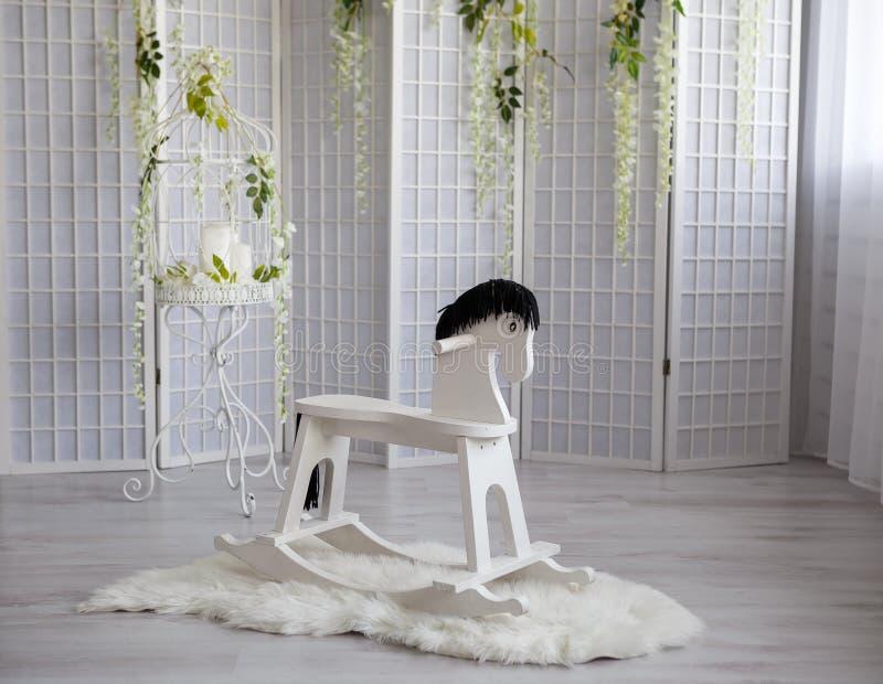 Cavalo de balanço do brinquedo na sala branca com parede branca imagem de stock