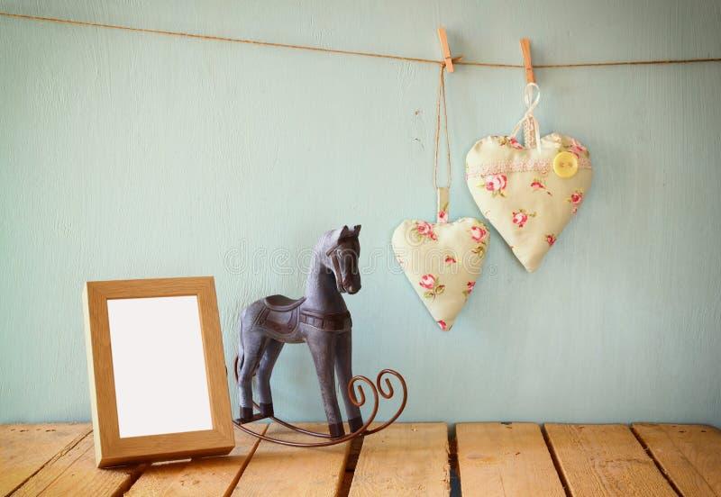 cavalo de balanço do vintage ao lado dos corações da tela que penduram na corda no assoalho de madeira e no quadro vazio da foto  imagem de stock
