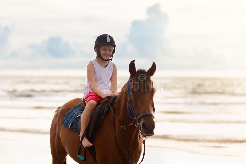 Cavalo de equitação das crianças na praia Cavalos do passeio das crian?as fotografia de stock