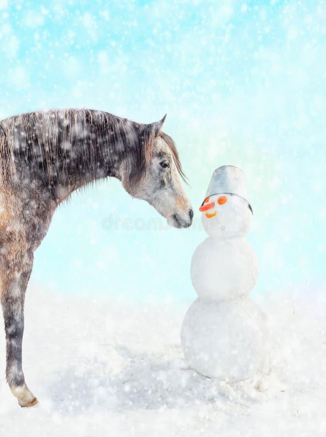 Cavalo e boneco de neve na queda da neve foto de stock