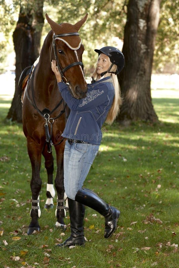 Cavalo fêmea do abraço do cavaleiro foto de stock