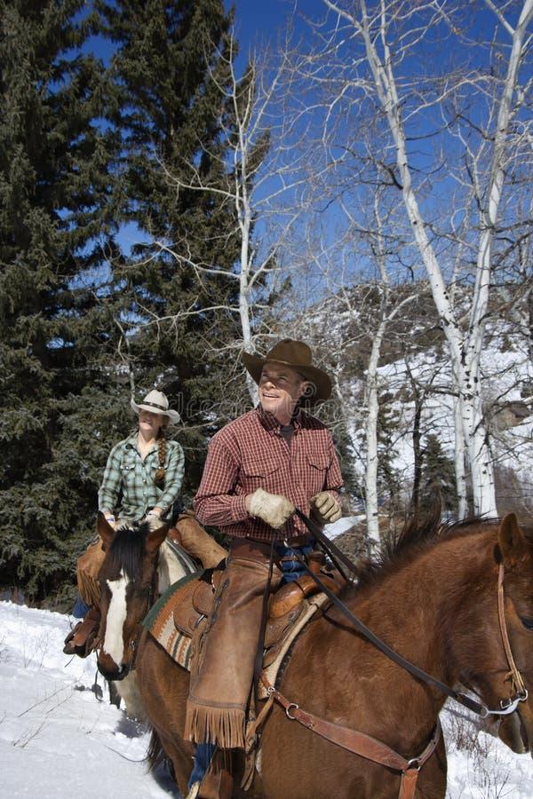 Cavalos de equitação do homem e da mulher na neve fotos de stock