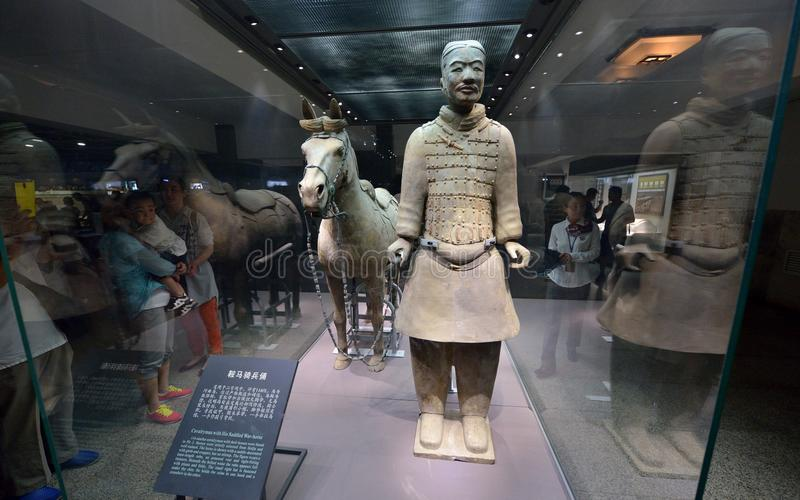 Cavalryman with his saddled war-horse. Tourist are taking photo and enjoying the terracotta warrior and horse in the mausoleum of the first Qin Emperor in China royalty free stock image