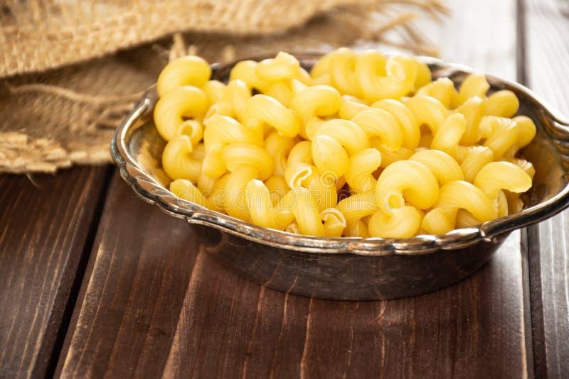 Cavatappi pasta som är rå på brunt trä arkivfoto