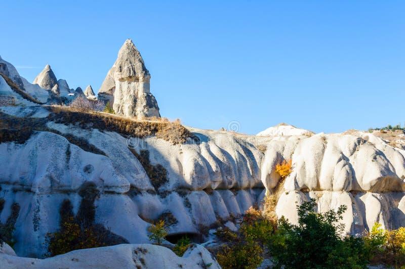 Cave as cidades na formação de rochas vulcânicas, casas de pedra em Goreme, paisagem da montanha cinzelada no tufo Cappadocia, Tu foto de stock