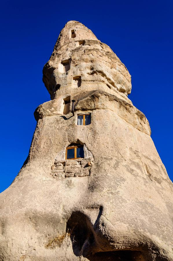 Cave as cidades na formação de rochas vulcânicas, casas de pedra em Goreme, paisagem da montanha cinzelada no tufo Cappadocia, Tu fotografia de stock