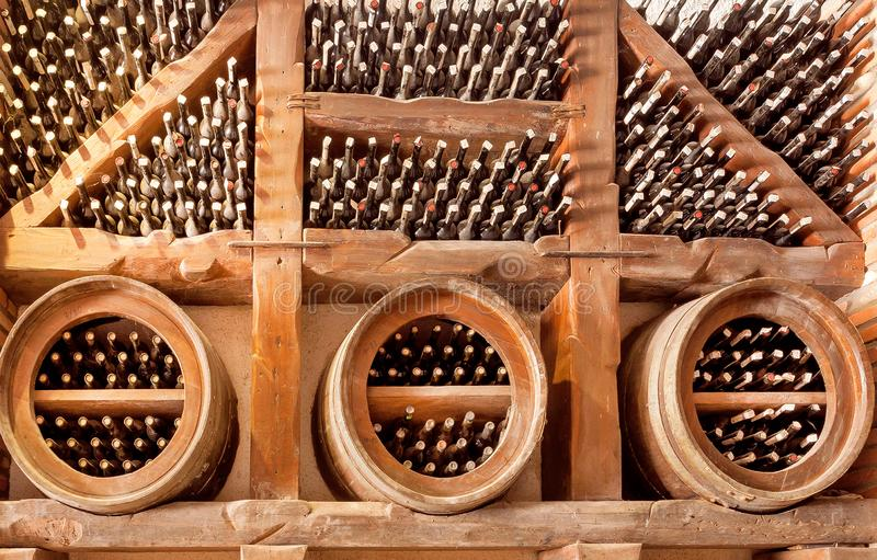 Cave avec des bouteilles dans les étagères en bois du souterrain rural de stockage ou de restaurant image stock