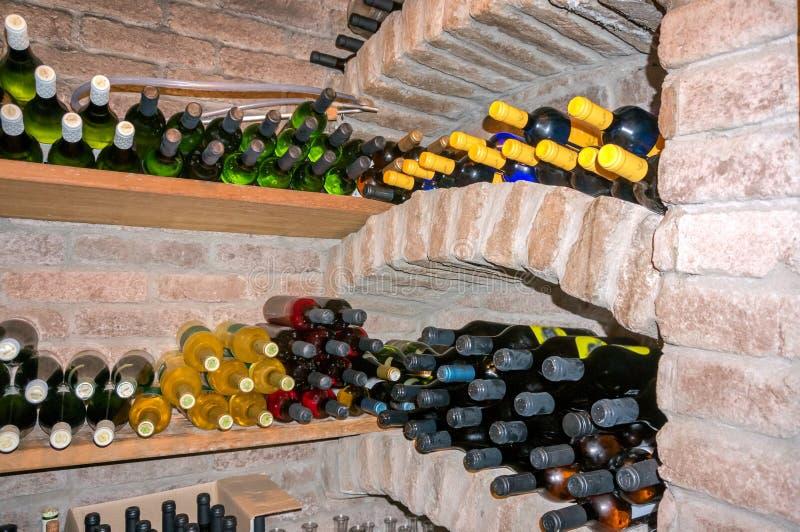 Cave avec des bouteilles de différents vins sur les étagères en bois photo libre de droits