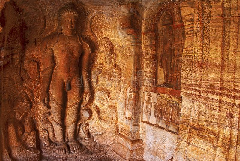 Cave 4 : Carved figure of Bahubali with his lower legs surrounded by snakes, together with his daughters Brahmi and Sundari.  royalty free stock images