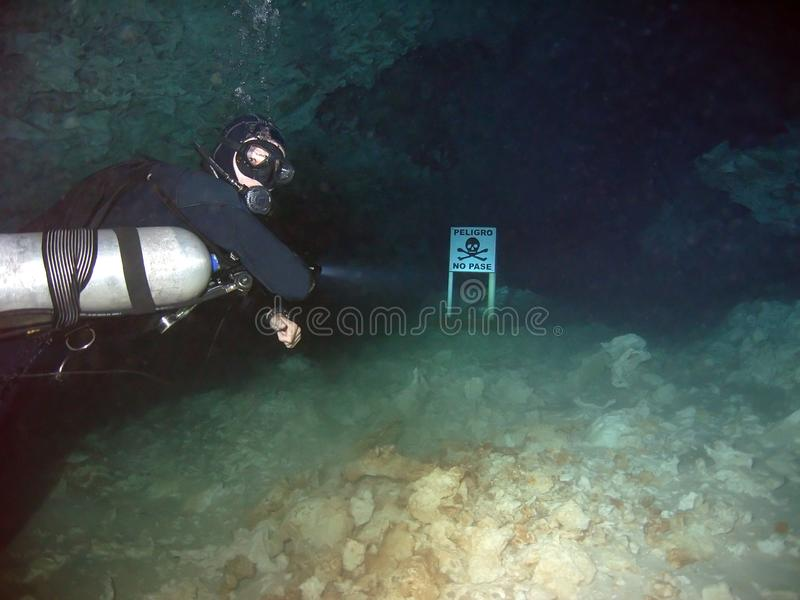 A Cave Diver Points Out Danger Sign. A cave diver shines his light on a `danger` warning sign that marks the end of a cenote cavern system & the beginning of a stock image