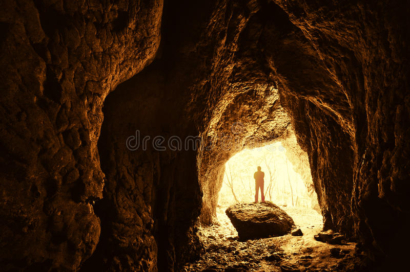 Cave entrance with silhouette of man stock image