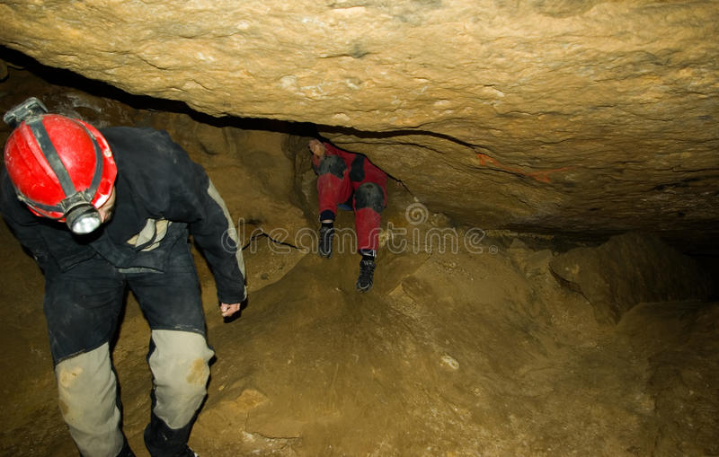 Cave exploration. Young men inside labyrinth of Pál-völgyi-Mátyás-hegyi cave system which is located in the Duna-Ipoly National Park. It is a real stock photo