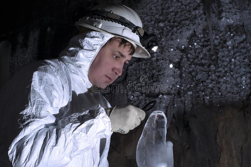 The cave explorer looks at the icy stalagmite royalty free stock photography
