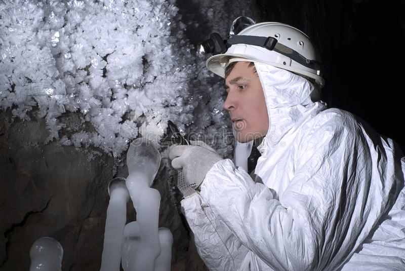 The cave explorer looks at the icy stalagmite stock image