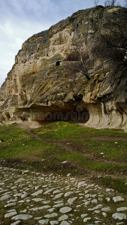 The cave is on a hillside in the ancient town Chufut-Kale in Crimea, near Bakhchisarai. Vertical view stock photography