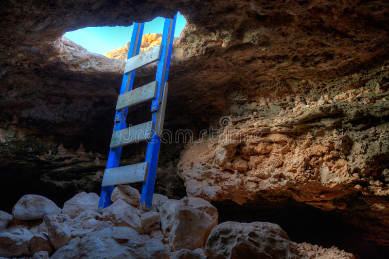 Cave hole entrance with ladder in Barbaria Cape royalty free stock image