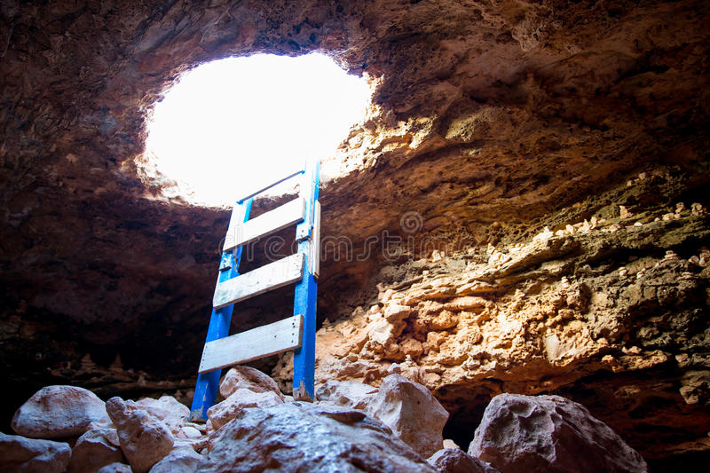 Cave hole entrance with ladder in Barbaria Cape. At formentera royalty free stock photos