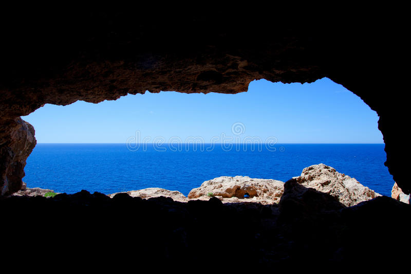 Cave hole in Formentera with blue sea view. Cave hole in Barbaria Cape Formentera with mediterranean blue sea view royalty free stock image
