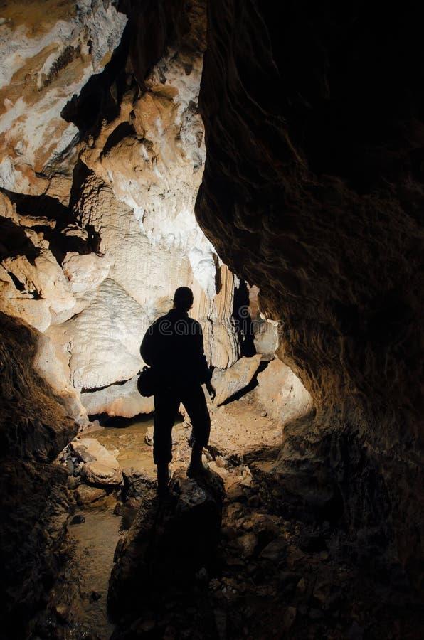 Cave with man silhouette explorer. Underground cave with man silhouette explorer stock photo
