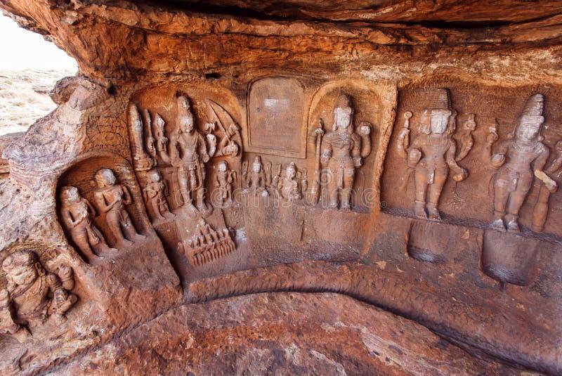 Cave o templo com esculturas hindu dos deuses na cidade de Badami, Índia Carvings do templo feitos no século VI, agora estado de  fotos de stock royalty free