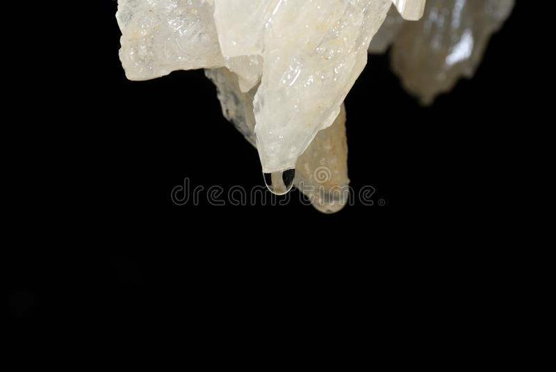 Cave stalactite. Ancient cave stalactite on the black stock image